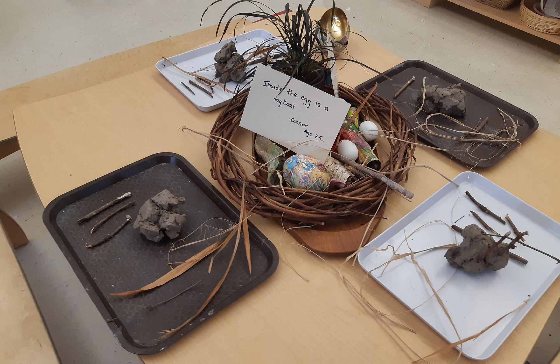 """A table set up with trays of various natural materials. There is a card which says """"Inside the egg is a toy boat"""""""